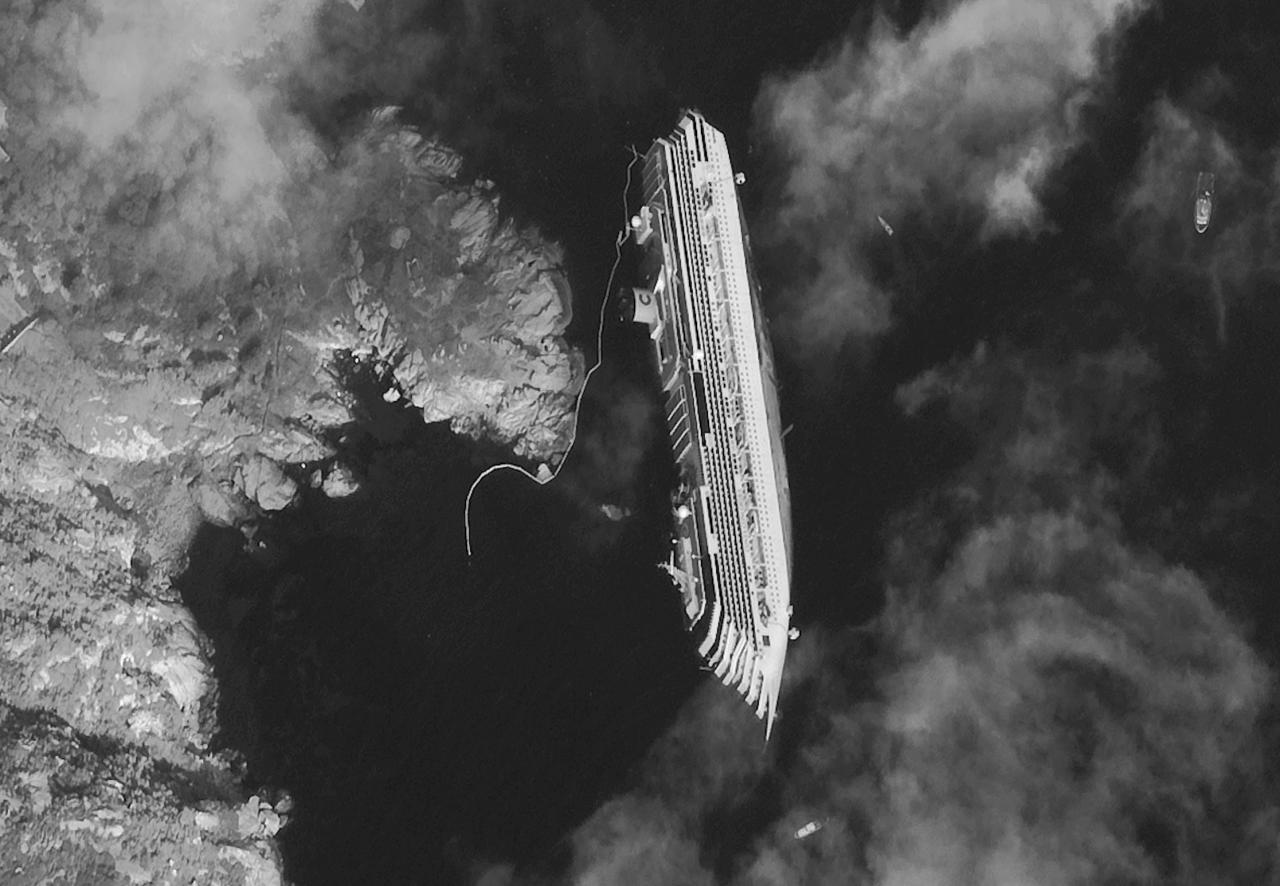 RETRANSMISSION FOR ALTERNATIVE CROP - This satellite image made Tuesday, Jan. 17, 2012, provided by DigitalGlobe on Wednesday, Jan. 18, 2012, shows the hulk of the luxury cruise ship Costa Concordia, which ran aground the Tuscan tiny island of Isola del Giglio, Italy, on Friday, leaning on its starboard side. As the Costa Concordia keeps shifting on its rocky ledge, many have raised the prospect of a possible environmental disaster if the 2,300 tonnes of fuel on the half-submerged cruise ship leaks. Satellites are used to monitor the area while authorities are preparing to remove the fuel from inside the vessel. (AP Photo/DigitalGlobe) MANDATORY CREDIT