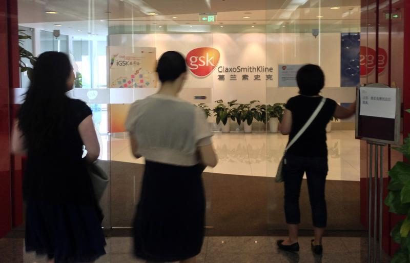 Chinese employees walk into a GSK office in Beijing