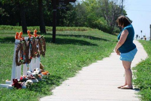 A woman stands with her head bowed after laying flowers at a makeshift memorial near the Sikh Temple of Wisconsin