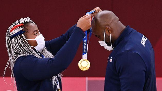 Gold medalist Teddy Riner of France, right, receives a medal from teammate Romane Dicko. France won gold in the mixed team judo competition on July 31. (Photo: Annegret Hilse via Reuters)