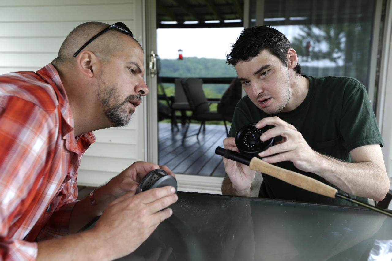 In this June 25, 2013 photo, Richard Norris, right, shows friend Andrew Kahle how to load line into a fly fishing rod at Norris' home in Hillsville, Va. Norris, whose face was disfigured by a gunshot, spent 15 years as a recluse, but now the 37-year-old is doing things he never would have before. (AP Photo/Chuck Burton)
