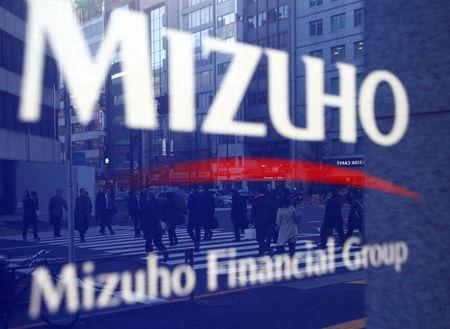 FILE PHOTO: Pedestrians are reflected on Mizuho Bank's signboard in Tokyo