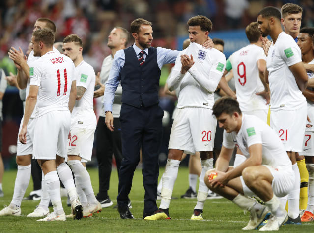 England head coach Gareth Southgate, center left, embraces England's Dele Alli at the end of the semifinal match between Croatia and England at the 2018 soccer World Cup in the Luzhniki Stadium in Moscow, Russia, Wednesday, July 11, 2018. (AP Photo/Rebecca Blackwell)