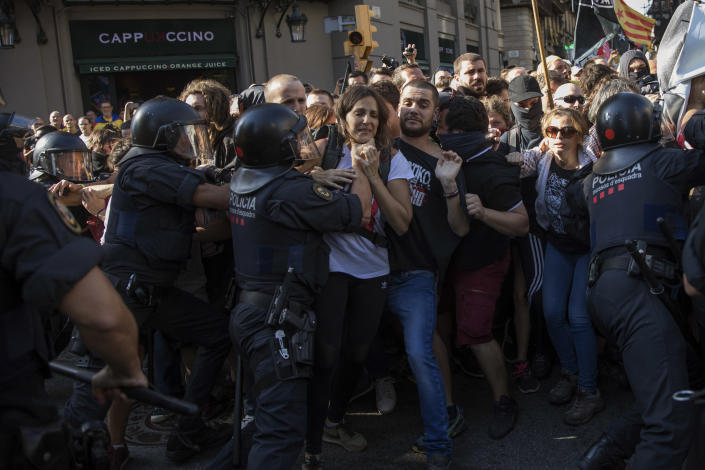 Catalan police officers clash with pro independence demonstrators on their way to meet a demonstrations by member and supporters of National Police and Guardia Civil in Barcelona on Saturday, Sept. 29, 2018. (AP Photo/Emilio Morenatti)