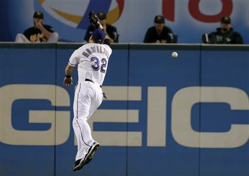Texas Rangers center fielder Josh Hamilton (32) leaps but is unable to reach a triple by Oakland Athletics' Derek Norris in the first inning of a baseball game as the Athletics bullpen watches, Wednesday, Sept. 26, 2012, in Arlington, Texas. (AP Photo/Tony Gutierrez)