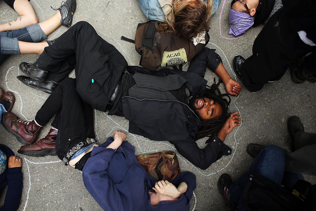 Protesters, many affiliated with the Occupy Wall Street movement, lay down while demonstrating in front of the Boeing headquarters on the second day of the NATO summit on May 21, 2012 in Chicago, Illinois. Sixty heads of state, 2,500 journalists and thousands of protesters have converged on Chicago for the two day NATO meeting which began on Sunday and looks to address the situation in Afghanistan among other global defense issues. Chicago police are preparing for the worst with many officers in riot gear and with their numbers enhanced by police from outside the city.  (Photo by Spencer Platt/Getty Images)