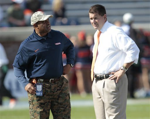 Virginia head coach Mike London, left, and Miami head coach Al Golden talk prior to the start of an NCAA college football game in Charlottesville, Va., Saturday, Nov. 10, 2012. (AP Photo/Steve Helber)