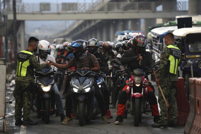 Police wearing protective gear inspect motorcycle riders at a checkpoint during a stricter lockdown as a precaution against the spread of the coronavirus on the outskirts of Marikina City, Philippines on Friday, August 6, 2021. Thousands of people jammed coronavirus vaccination centers in the Philippine capital, defying social distancing restrictions, after false news spread that unvaccinated residents would be deprived of cash aid or barred from leaving home during a two-week lockdown that started Friday. (AP Photo/Basilio Sepe)