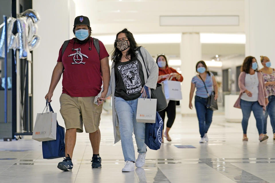 Mask-wearing shoppers make their way down a concourse at the American Dream Mall, Thursday, Oct. 1, 2020, in East Rutherford, New Jersey, after the megamall reopened to the public. The complex was set to have a grand opening for dozens of retailers on March 19. But the mall shut down completely on March 16, as the country began to go on lockdown due tp concerns over the spread of the coronavirus. (AP Photo/Kathy Willens)