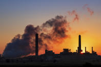 FILE - In this July 27, 2018, file photo, the Dave Johnson coal-fired power plant is silhouetted against the morning sun in Glenrock, Wyo. A law signed April 6, 2021, by Republican Gov. Mark Gordon creates a $1.2 million fund for an initiative that marks the latest attempt by state leaders to help coal in the state that accounts for the bulk of U.S. coal production, which is down by half since 2008. Wyoming coal production, which accounts for about 40% of the nation's total, has declined as utilities switch to gas, which is cheaper to burn to generate electricity. Solar and wind power also are on the rise as coal's share of the U.S. power market shrinks from about half in the early 2000s to less than 20% now. (AP Photo/J. David Ake, File)