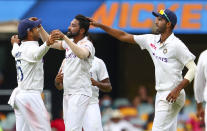India's Mohammed Siraj, centre, celebrates with teammate Mayank Agarwal, left, after taking his fifth wicket during play on day four of the fourth cricket test between India and Australia at the Gabba, Brisbane, Australia, Monday, Jan. 18, 2021. (AP Photo/Tertius Pickard)