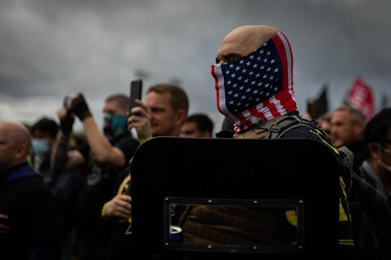A man in a U.S. flag mask and carrying a riot shield holds his hand to his heart