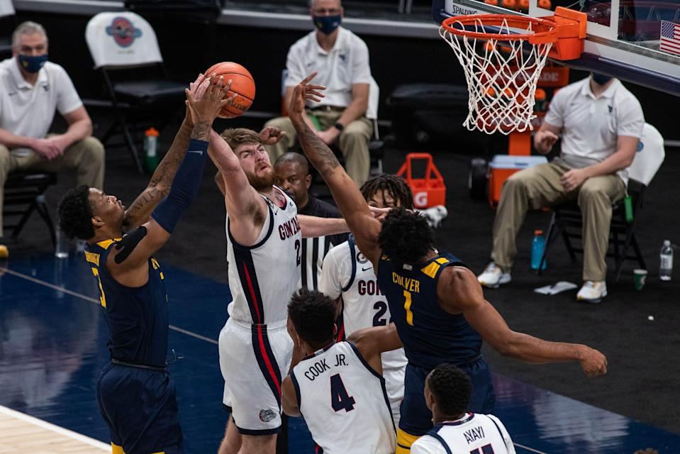 Gonzaga forward Drew Timme (2) rebounds the ball over West Virginia forward Gabe Osabuohien (3) and forward Derek Culver (1) in the second half at Bankers Life Fieldhouse.