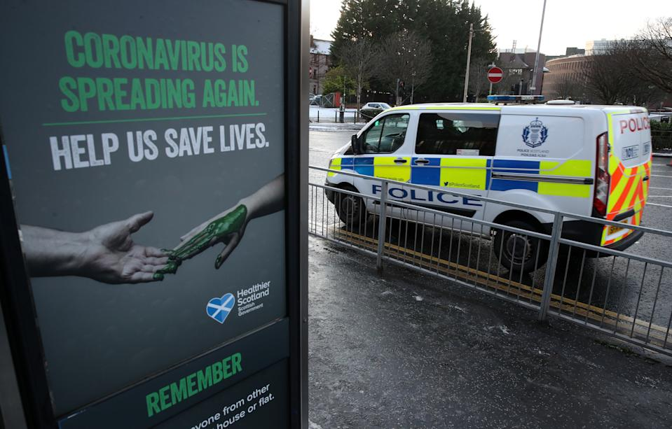 A police vehicles passes a Coronavirus related poster on a phone box outside Glasgow Royal Infirmary after severe lockdown restrictions were announced for December and January with all of the country moving into the highest level of lockdown from Boxing Day.