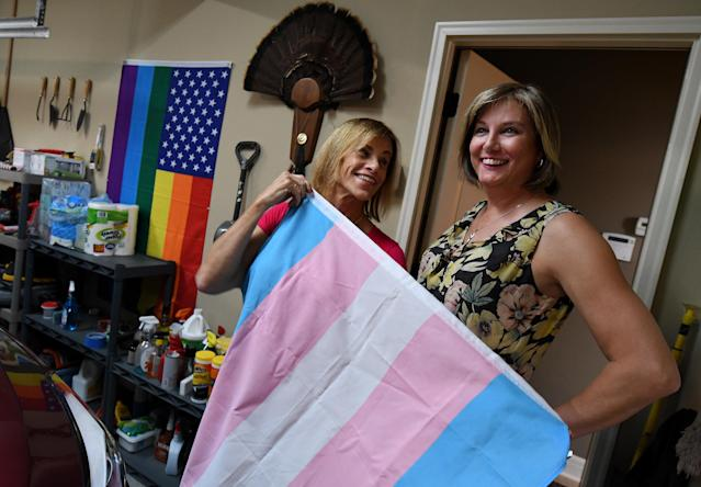 In the garage at their Shawnee home, Suzanne Wheeler and her fiancee, Marsha Riley, show off a transgender flag, with a gay pride flag on the wall. (Jill Toyoshiba for HuffPost)