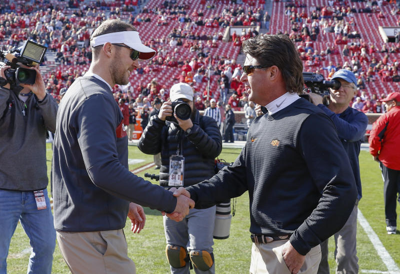 Oklahoma head coach Lincoln Riley, left, and Oklahoma State head coach Mike Gundy, right, meet mid field before the start of an NCAA college football game in Norman, Okla., Saturday, Nov. 10, 2018. (AP Photo/Alonzo Adams)