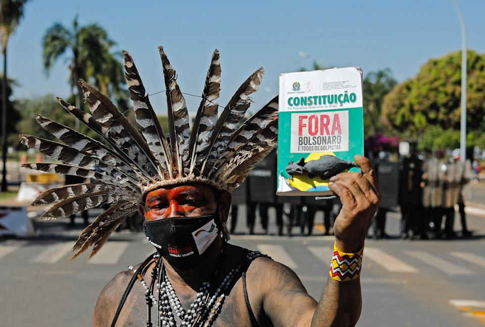 An indigenous man shows a copy of the Constitution reading Bolsonaro and all those in favour of the coup, out, referring to Brazilian President Jair Bolsonaro, during a protest outside the National Congress in Brasilia, on June 22, 2021. - Indigenous people are camping in the capital to oppose a bill said to limit recognition of reserve lands. (Photo by Sergio Lima / AFP) (Photo by SERGIO LIMA/AFP via Getty Images)