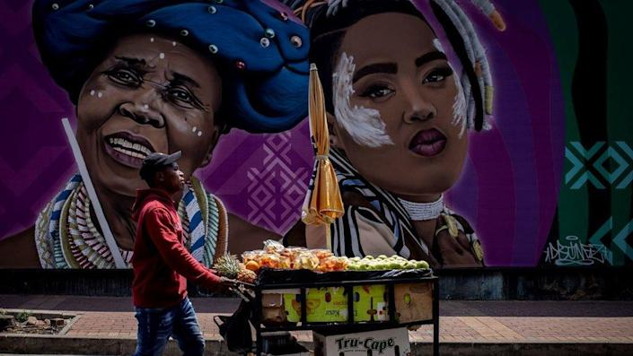 Man with a mobile fruit stall walking past a large street art mural. The mural shows two women. One is an elderly woman who is smiling. She has on a blue headdress and traditional neck adornments, the other lady is younger. She is pouting and has some white face paint on