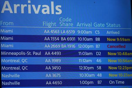 FILE PHOTO: An American Airlines arrivals board displaying American Airlines flight 2669, which was scheduled to be flown by a Boeing 737 Max 8, arriving from Miami to New York City at LaGuardia Airport, is seen as cancelled, in New York, U.S., March 14, 2019. REUTERS/Shannon Stapleton/File Photo/File Photo