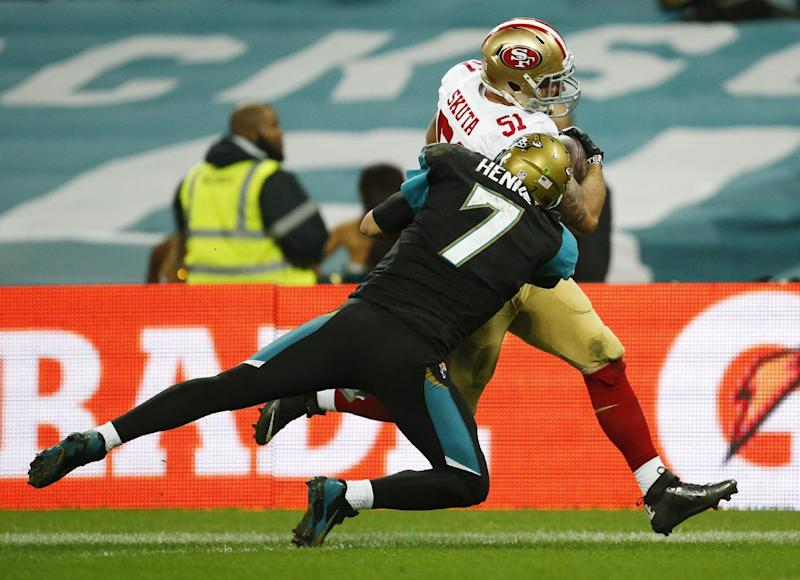 CORRECTS WHO RECOVERED A FUMBLE FROM SAN FRANCISCO 49ERS TIGHT END VANCE MCDONALD TO JACKSONVILLE JAGUARS TIGHT END MARCEDES LEWIS - Jacksonville Jaguars quarterback Chad Henne (7) tries to tackle San Francisco 49ers outside linebacker Dan Skuta (51) as he scores on a 47-yard touchdown run after recovering a fumble by Jacksonville Jaguars tight end Marcedes Lewis during the second half of an NFL football game at Wembley Stadium, London, Sunday, Oct. 27, 2013. (AP Photo/Matt Dunham)