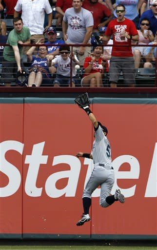 Seattle Mariners' Ichiro Suzukii chases down a fly out by Texas Rangers' Nelson Cruz in the eighth inning of a baseball game Thursday, April 12, 2012, in Arlington, Texas. The Rangers won 5-3. (AP Photo/Tony Gutierrez)