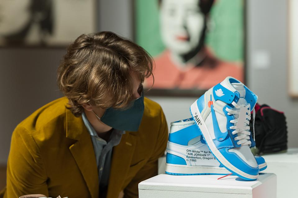 LONDON, UNITED KINGDOM - OCTOBER 01, 2020: A gallery staff member looks at A pair of off-white X Nike Air Jordan 1 UNC 'Revealing', 2018, (estimated sale price £2,000 - 2,200)during a photo call for Bonhams' Pop x Culture sale, on October 01, 2020 in London, England.- PHOTOGRAPH BY Wiktor Szymanowicz / Barcroft Studios / Future Publishing (Photo credit should read Wiktor Szymanowicz/Barcroft Media via Getty Images)