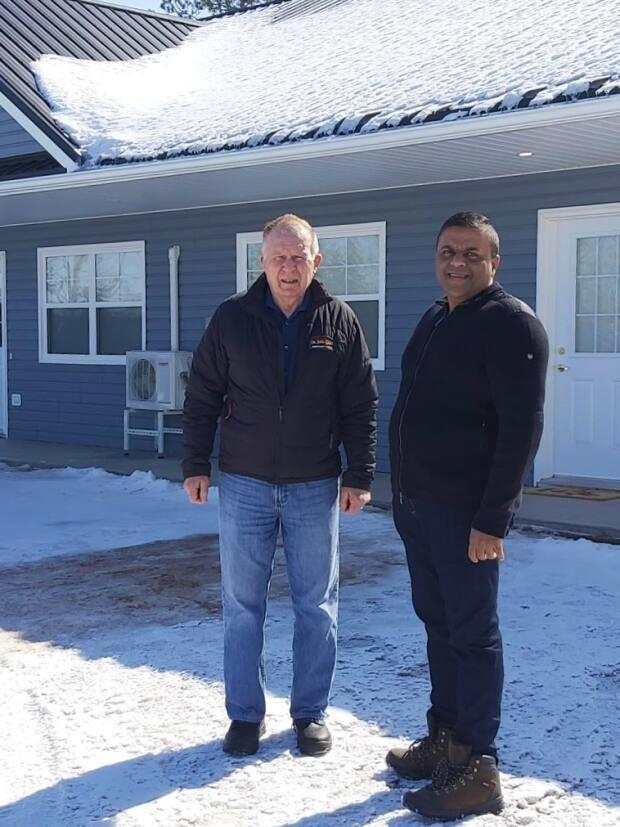 Owner of Dr. John M. Gillis Memorial Lodge, Douglas MacKenzie, and Ajay Punnapadam standing in front of the new Gillis Place apartments.