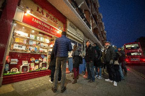 Customers queue early in the morning to buy a copy of the French satirical magazine Charlie Hebdo, in London on January 16, 2015