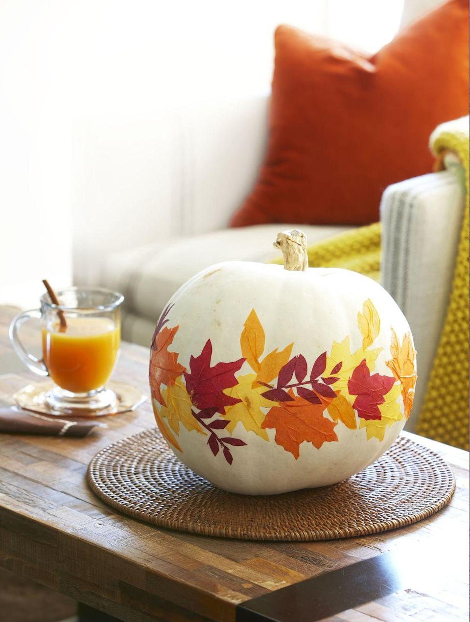 """<p>Paper leaves encircling a white pumpkin make a graphic statement. Trace fallen leaves onto orange, yellow, and dark red tissue paper; cut tracings out and stick them to pumpkin using decoupage glue. With a flat-head bristle brush, push from leaves' outer edges toward the centers to pucker paper slightly and create """"veins""""; let dry. Brush a thin layer of glue over pumpkin.</p>"""