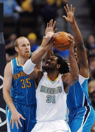 Denver Nuggets forward Nene, center, of Brazil, tries to put up a shot through the defense of New Orleans Hornets center Chris Kaman, left, and forward Carl Landry, right, in the first quarter of an NBA basketball game Monday, Jan. 9, 2012, in Denver. (AP Photo/Chris Schneider)