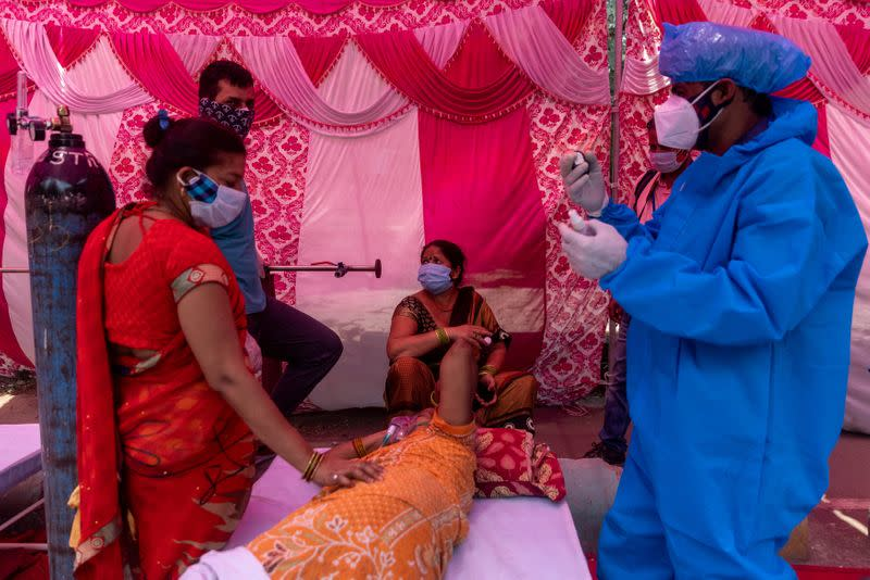 A woman surrounded by her relatives receives oxygen support for free at a Gurudwara in Ghaziabad