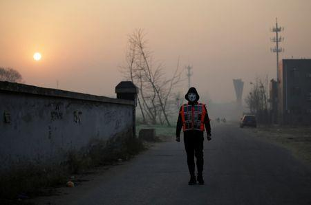 Artist Liu Bolin wearing a vest with 24 mobile phones walks in smog as he live broadcasts air pollution in the city on the fourth day after a red alert was issued for heavy air pollution in Beijing, China, December 19, 2016. REUTERS/Jason Lee