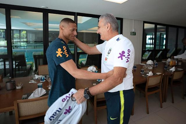 Happy to see you: the Brazilian Football Confederation released a photo showing coach Tite greeting Richarlison, the first player to turn up at a sparsely attended training camp (AFP Photo/Lucas FIGUEIREDO)
