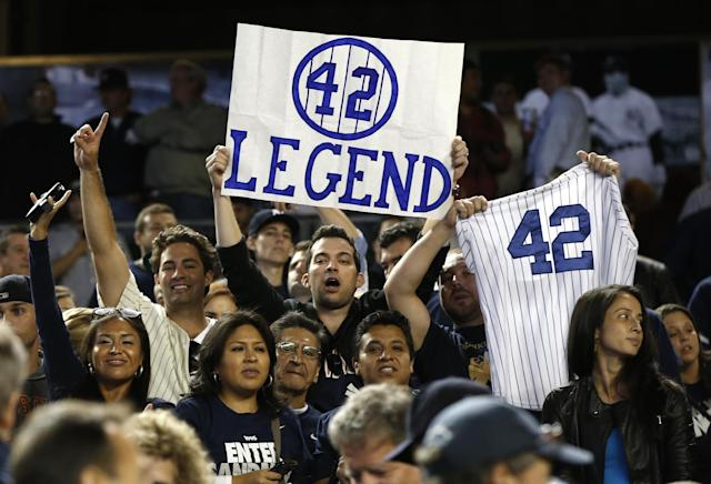 Fans of New York Yankees relief pitcher Mariano Rivera (42) hold signs after Rivera's final appearance at a baseball game at Yankee Stadium, Thursday, Sept. 26, 2013, in New York. (AP Photo/Kathy Willens)