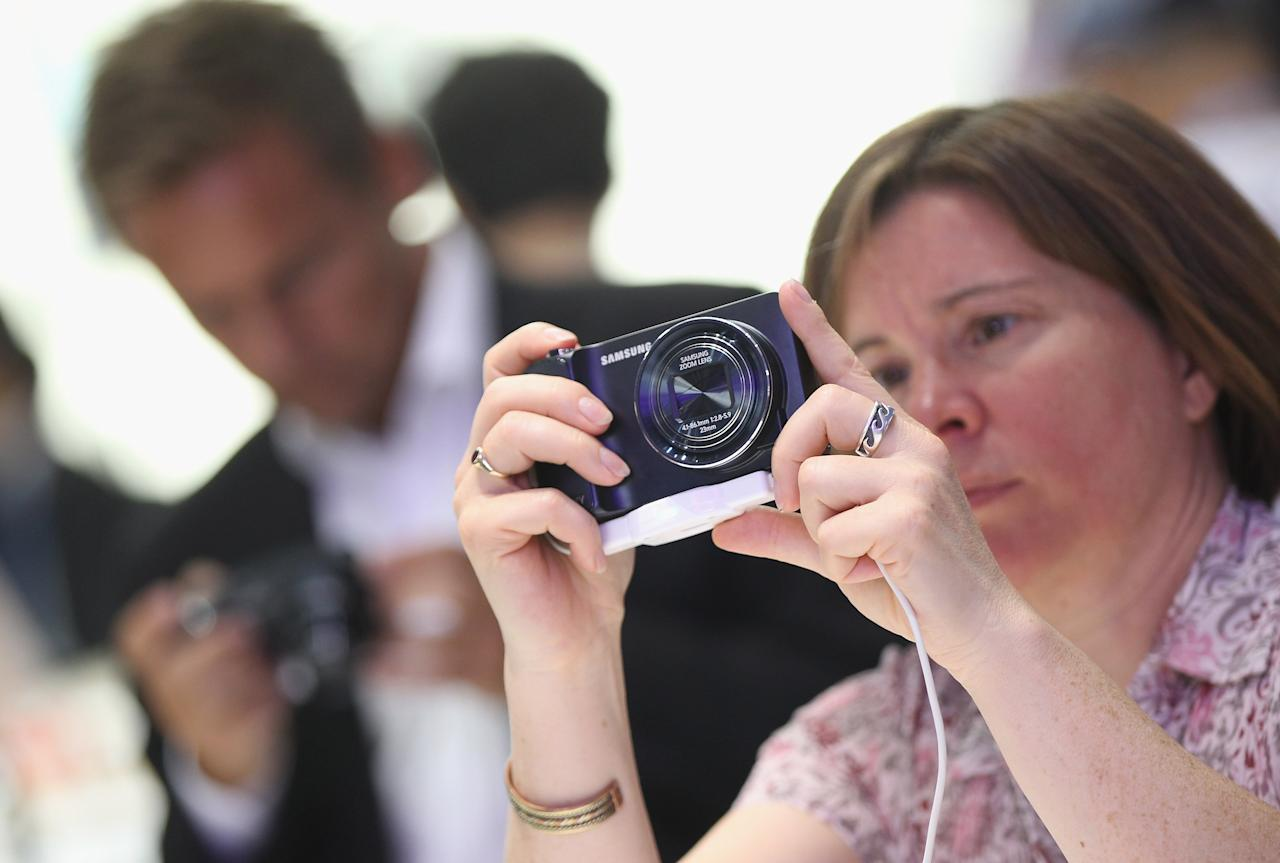 BERLIN, GERMANY - AUGUST 30:  Visitors try out the new Samsung Galaxy Camera, which combines a smartphone and a digital camera with a zoom lens, during a press day at the Samsung stand at the IFA 2012 consumer electronics trade fair on August 30, 2012 in Berlin, Germany. IFA 2012 will be open to the public from August 31 through September 5.  (Photo by Sean Gallup/Getty Images)