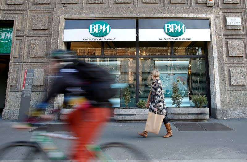 A woman walks in front of the Banca Popolare di Milano (BPM) bank in downtown Milan