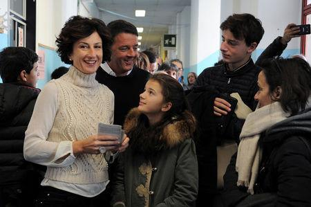 Italian Prime Minister Matteo Renzi and his wife Agnese (L) smile as they wait to cast their votes with they children during the referendum on constitutional reform, in Pontassieve, near Florence, northern Italy December 4, 2016. REUTERS/Paolo Lo