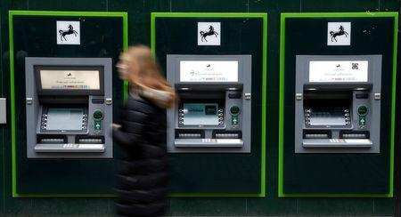 FILE PHOTO: A woman walks past a row of cash machines outside a branch of Lloyds Bank in Manchester, Britain, February 21, 2017. REUTERS/Phil Noble