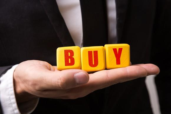 Bright yellow blocks spelling out the word buy in red letters, while resting on a man's right hand.