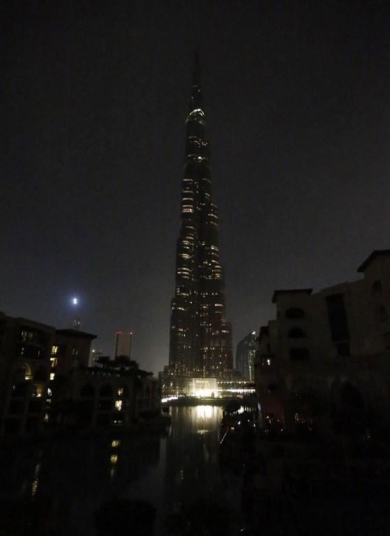 "'The lights on the Burj Khalifa tower are switched off for an hour in Downtown Dubai, on March 23, 2013, as iconic landmarks and skylines are plunged into darkness as the ""Earth Hour"" switch-off of lights around the world got under way to raise awareness of climate change. AFP PHOTO/KARIM SAHIB"