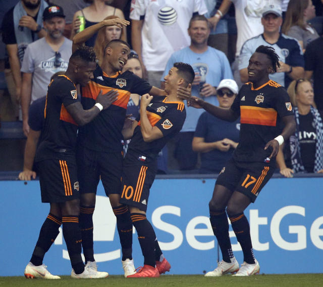 Houston Dynamo forward Mauro Manotas, second from left, celebrates his goal with teammates Romell Quioto, left, Tomas Martinez (10) and Alberth Elis (17) during the first half of an MLS soccer match against Sporting Kansas City in Kansas City, Kan., Saturday, June 23, 2018. (AP Photo/Orlin Wagner)