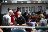 North Carolina State personnel chat in the dugout during a delay due to COVID-19 safety protocols before their baseball game against Vanderbilt in the College World Series Friday, June 25, 2021, at TD Ameritrade Park in Omaha, Neb. (AP Photo/Rebecca S. Gratz)