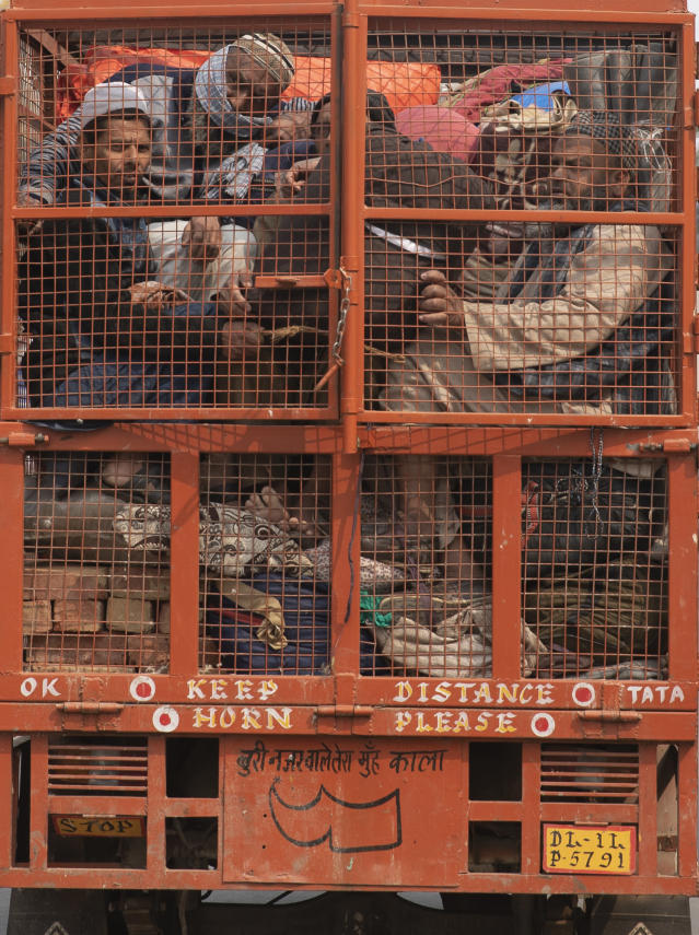 A group of Muslims huddle together in the back of a mini truck and leave the area after Tuesday's violence in New Delhi, India, Wednesday, Feb. 26, 2020. At least 20 people were killed in three days of clashes in New Delhi, with the death toll expected to rise as hospitals were overflowed with dozens of injured people, authorities said Wednesday. The clashes between Hindu mobs and Muslims protesting a contentious new citizenship law that fast-tracks naturalization for foreign-born religious minorities of all major faiths in South Asia except Islam escalated Tuesday. (AP Photo/Rajesh Kumar Singh)