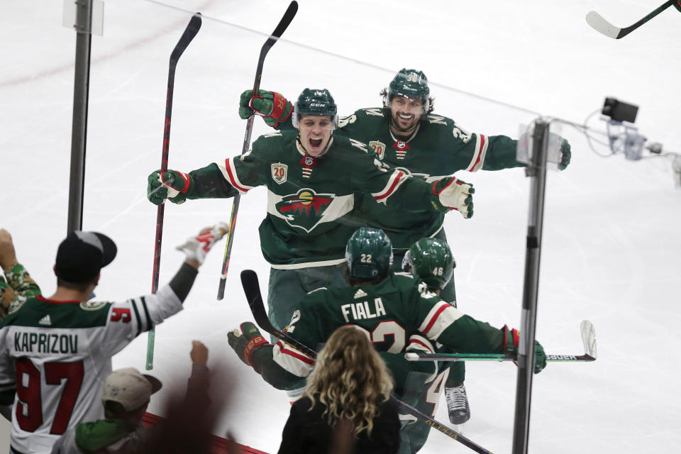 Minnesota Wild left wing Kevin Fiala (22) is congratulated by Joel Eriksson Ek (14) and Mats Zuccarello (36) after scoring a goal against the Vegas Golden Knights during the third period in Game 6 of an NHL hockey Stanley Cup first-round playoff series Wednesday, May 26, 2021, in St. Paul, Minn. The Wild won 3-0. (AP Photo/Andy Clayton-King)