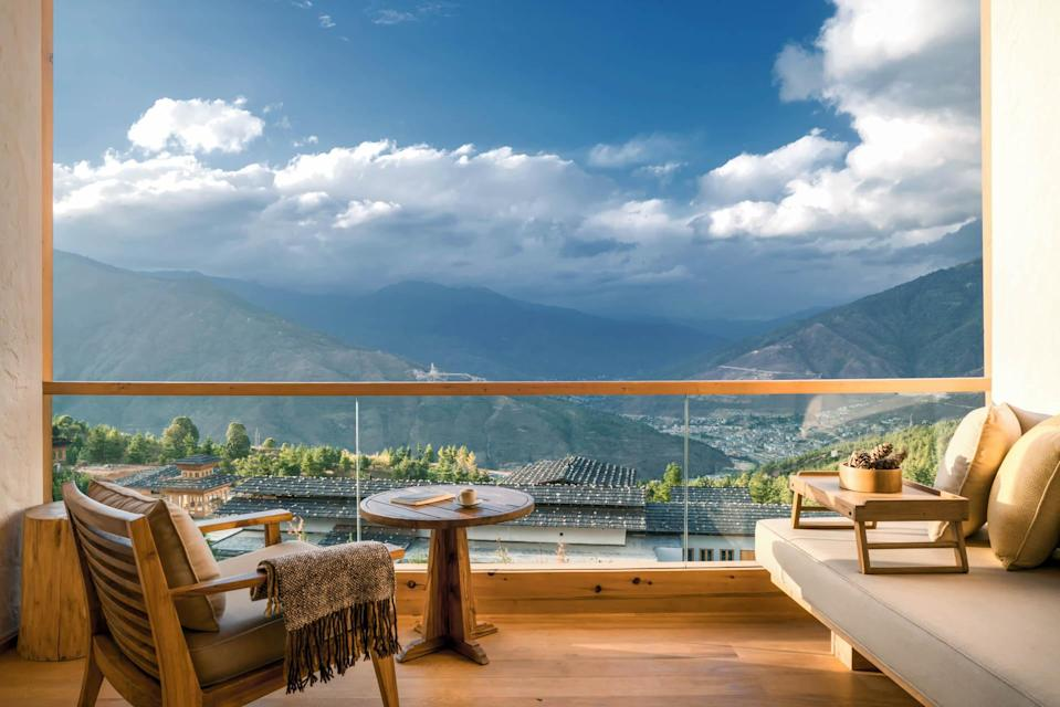 """<p><strong>Set the scene</strong> The Punakha valley landscape is lush and tropical, all forest-covered mountains hidden behind low-lying early-morning mist, terraced rice paddies, and vivid green patchwork hills. This lodge is part of the new Six Senses Bhutan five-strong circuit, a hugely long-awaited addition to the kingdom's other similarly aligned hotel brands, including COMO and Aman. Now that it's here, Six Senses fits in as beautifully as expected, and even though the Punakha lodge is technically much larger than the two previously mentioned big-hitters, it still manages to pull off an extremely intimate feel.</p> <p><strong>What's the backstory?</strong> Six Senses has long been known for its wellness-first approach and culturally considered design, both of which neatly align with the spiritual beliefs of the <a href=""""https://www.cntraveler.com/story/how-bhutan-avoids-being-overrun-by-tourists?mbid=synd_yahoo_rss"""" rel=""""nofollow noopener"""" target=""""_blank"""" data-ylk=""""slk:Bhutanese"""" class=""""link rapid-noclick-resp"""">Bhutanese</a> (they focus on putting other people first, rather than material possessions) and the nation's Gross National Happiness index. Built in collaboration with Bangkok-based Habita Architects, each lodge takes design cues from its surroundings. In Punakha that translates to a living room and bar (named the Flying Farmhouse and based on nearby traditional farmhouses) cantilevered over the pool, a simple restaurant with a pool-facing terrace, and a spa.</p> <p><strong>What can we expect in our room?</strong> The handful of rooms are split across a series of buttermilk-colored buildings that zigzag up a hill. Birch-white wood reigns; there's a traditional <em>bukhari</em> stove for chilly nights (it gets surprisingly cold), yellow-cushioned armchairs for lounging, and a private balcony with knockout views down into the emerald valley.</p> <p><strong>How about the food and drink?</strong> There's a help-yourself fruit station in the restaurant for """