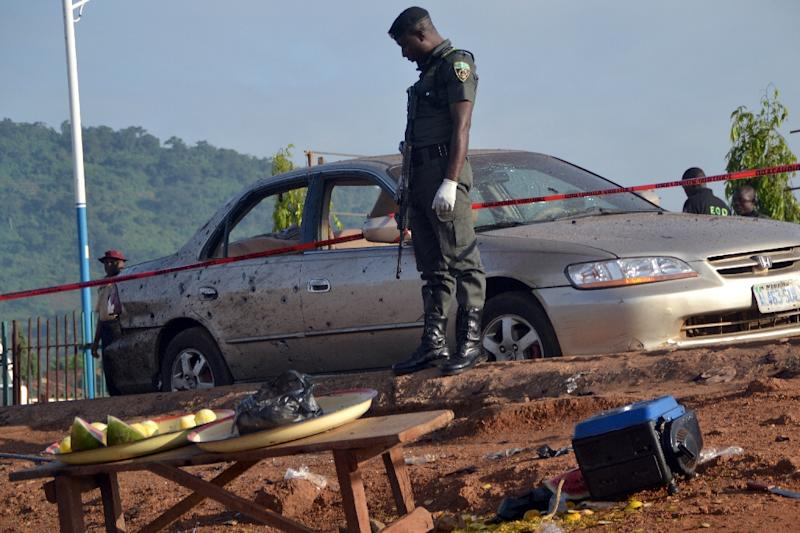 A Nigerian policeman stands beside a damaged car in Nyanya, near Abuja, on October 3, 2015, after two bomb blasts (AFP Photo/)
