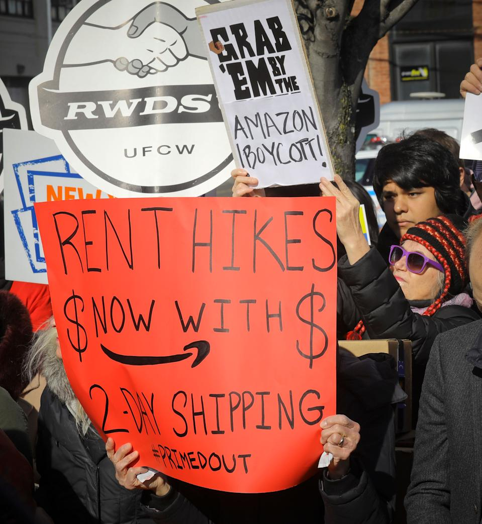 Protesters carry anti-Amazon signs during a coalition rally and press conference of elected officials, community organizations and unions opposing Amazon headquarters getting subsidies to locate in the New York neighborhood of Long Island City, Queens, Wednesday Nov. 14, 2018, in New York. (AP Photo/Bebeto Matthews)