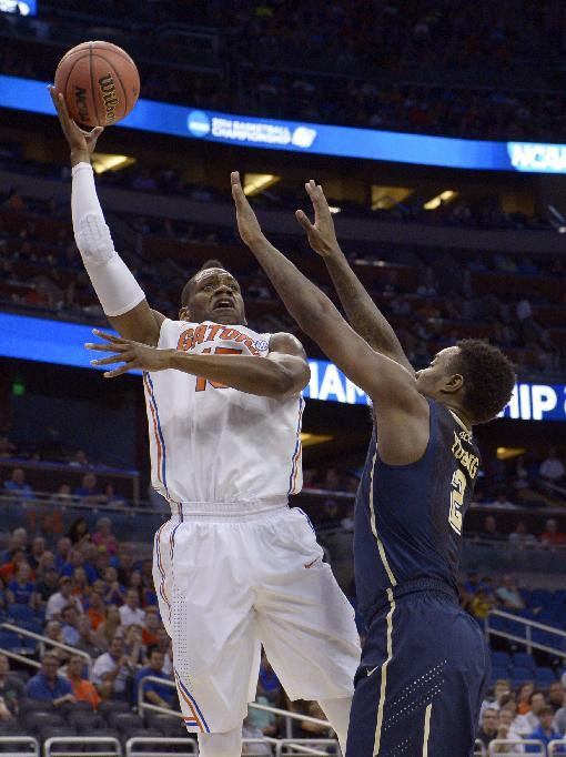 Florida forward Will Yeguete (15) aims for the basket over Pittsburgh forward Michael Young (2), during the first half in a third-round game in the NCAA college basketball tournament, Saturday, March 22, 2014, in Orlando, Fla. (AP Photo/Phelan M. Ebenhack)