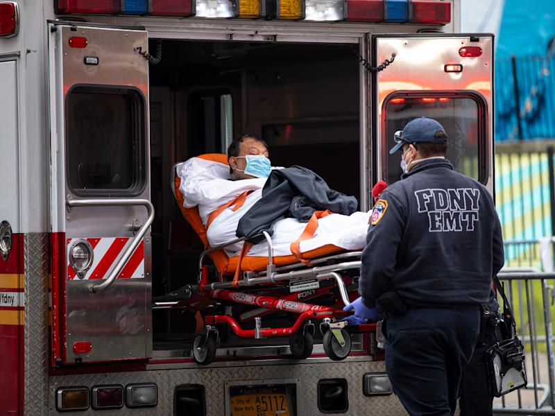 "QUEENS, NEW YORK - MARCH 30: Two members of the Fire Department of New York""u2019s Emergency Medical Team wheel in a patient with potentially fatal coronavirus to the Elmhurst Hospital Center in the Queens borough of New York City on March 30, 2020. New York City is the epicenter of the coronavirus pandemic in the United States, putting historic pressure on a world-renowned healthcare system as the number of confirmed cases in the area grows. (Photo by Robert Nickelsberg/Getty Images)"