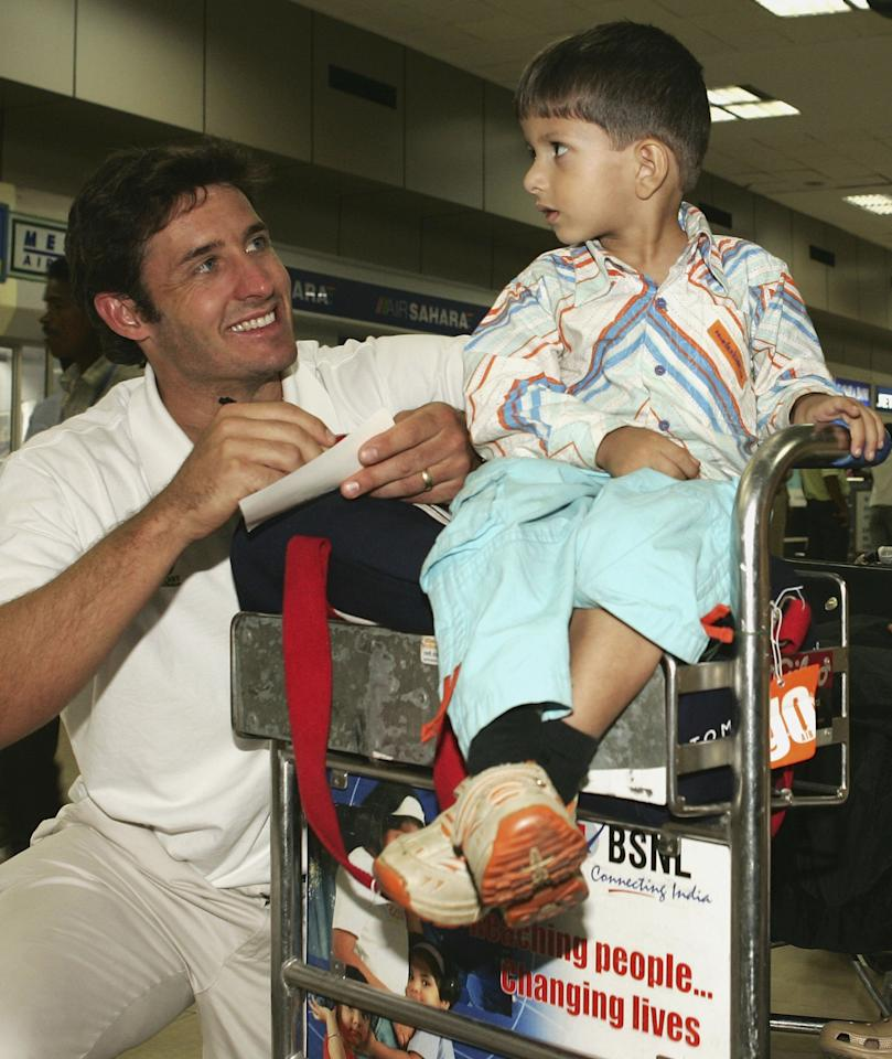 NEW DELHI, INDIA - OCTOBER 23:  Mike Hussey of Australia signs an autograph for young fan, Siddharth Rana, in New Delhi airport while the Australia team stop over on their trip from Jaipur to Chandigarh on October 23, 2006, in New Delhi, India.  (Photo by Hamish Blair/Getty Images)